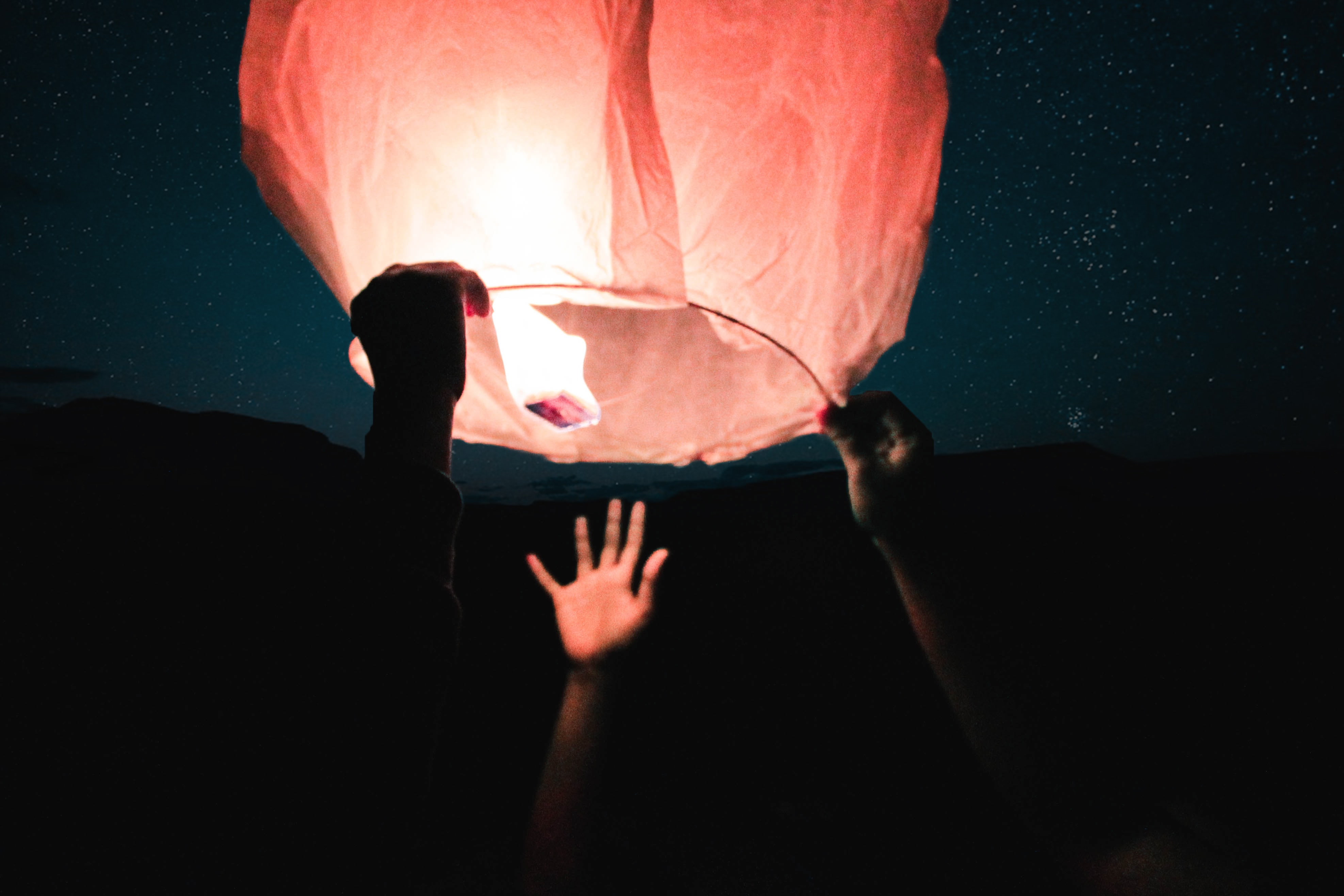 three human hand about to catch and hold sky lantern at night time