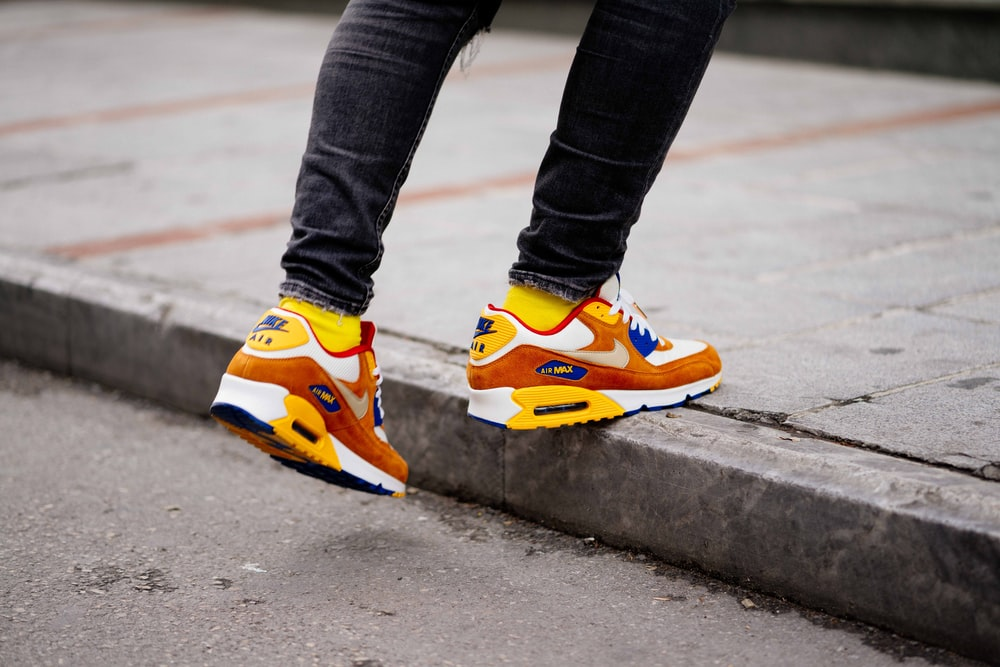 buy popular eb436 f9063 person wearing pair of orange-and-white Nike Air Max low-top shoes