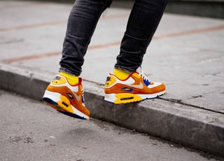 person wearing pair of orange-and-white Nike Air Max low-top shoes