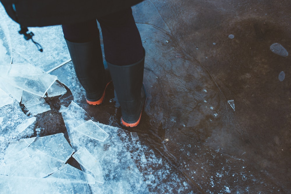 person standing near glass of ice