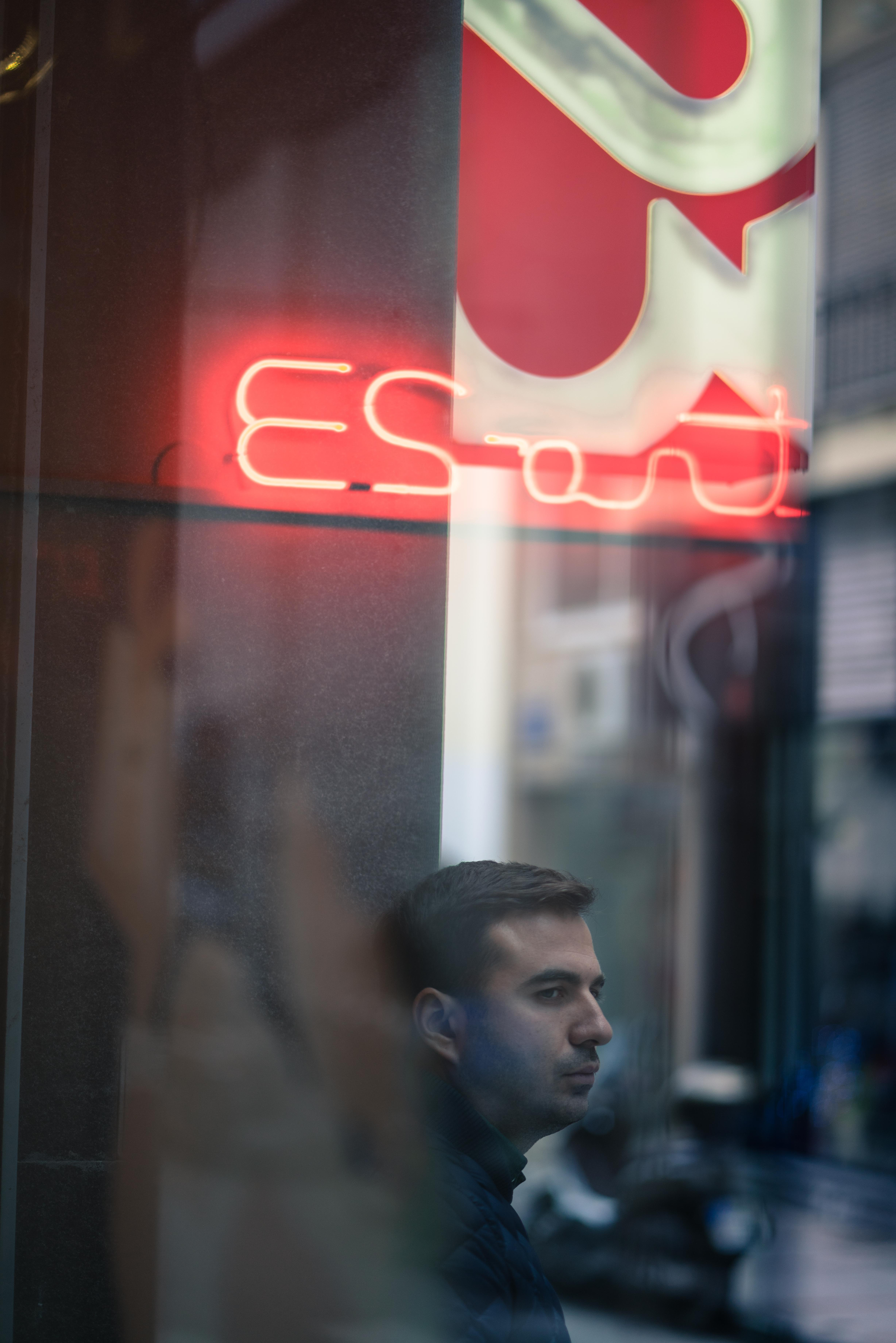 man wearing black jacket standing near signage and building at daytime
