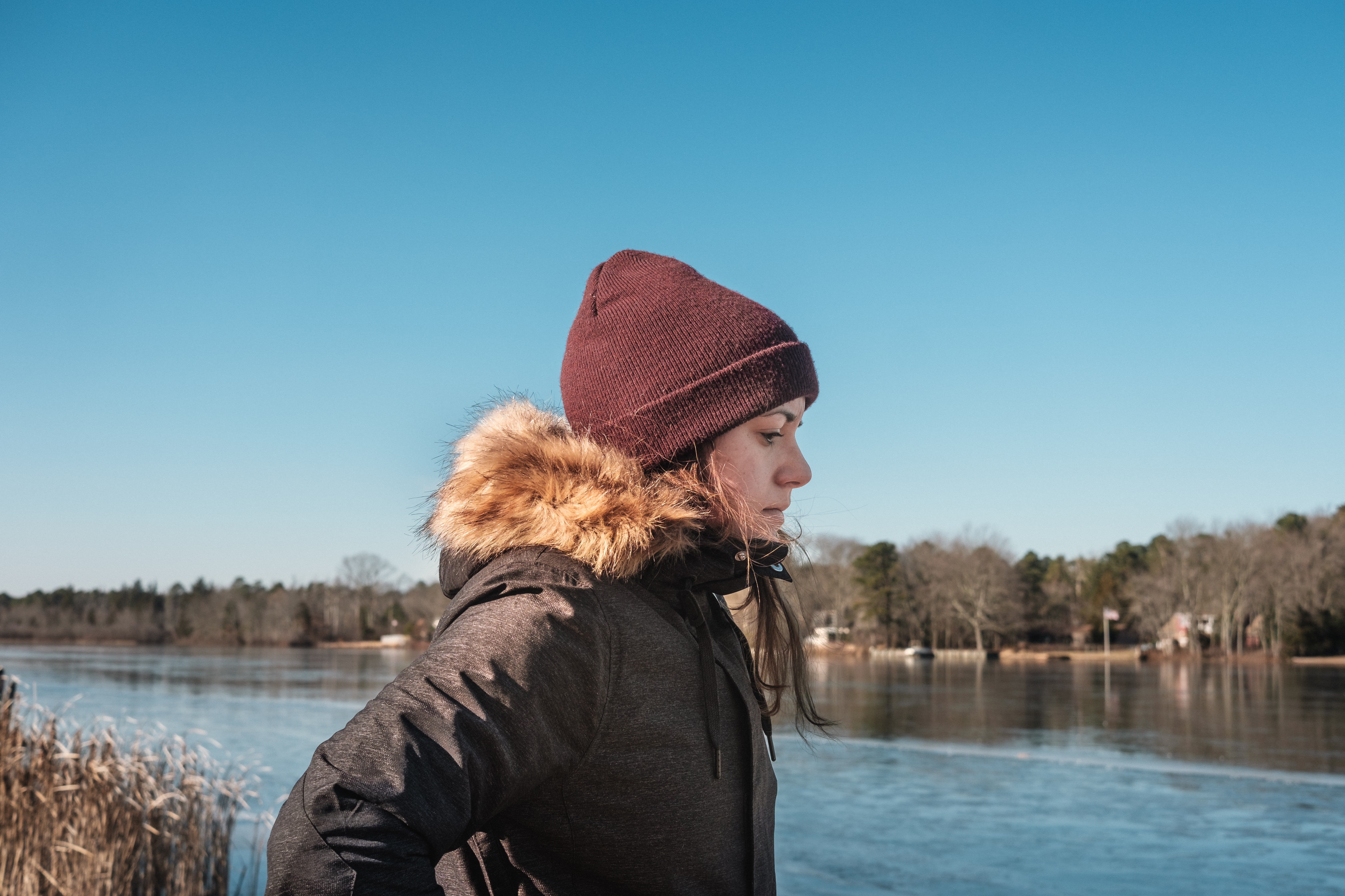 woman in brown knit cap standing beside body of water