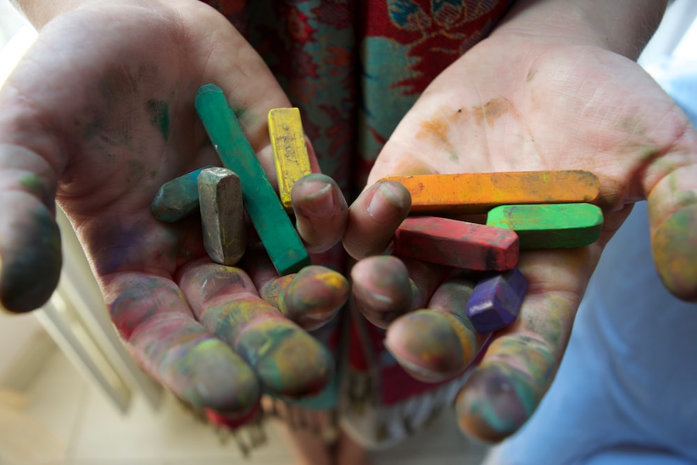 person holding assorted-color chalks