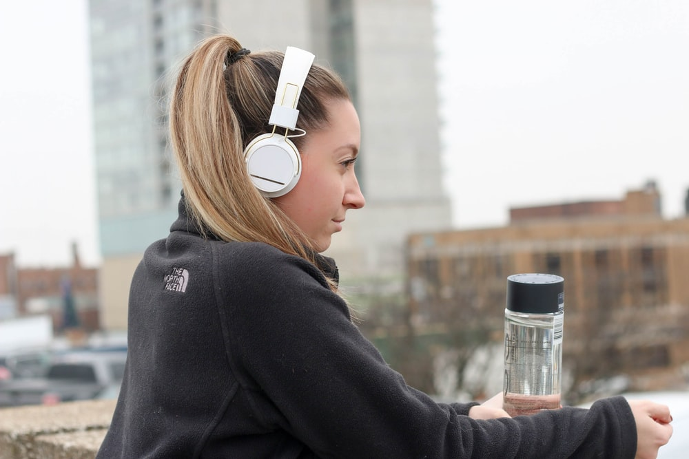 woman wearing black The North Face jacket and white headphones