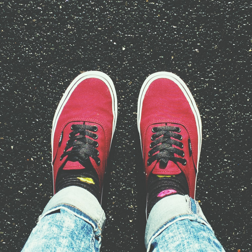 person in blue denim jeans and red and white sneakers