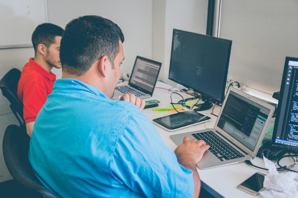 two men using laptop