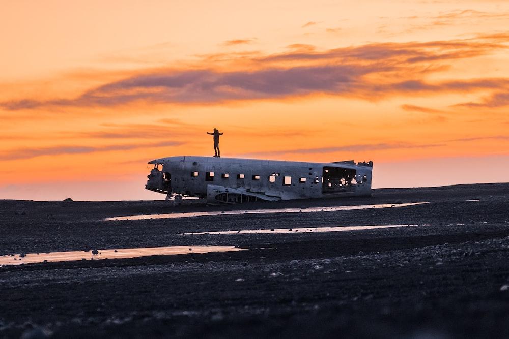 wrecked airplane on ground under clouds during golden hour