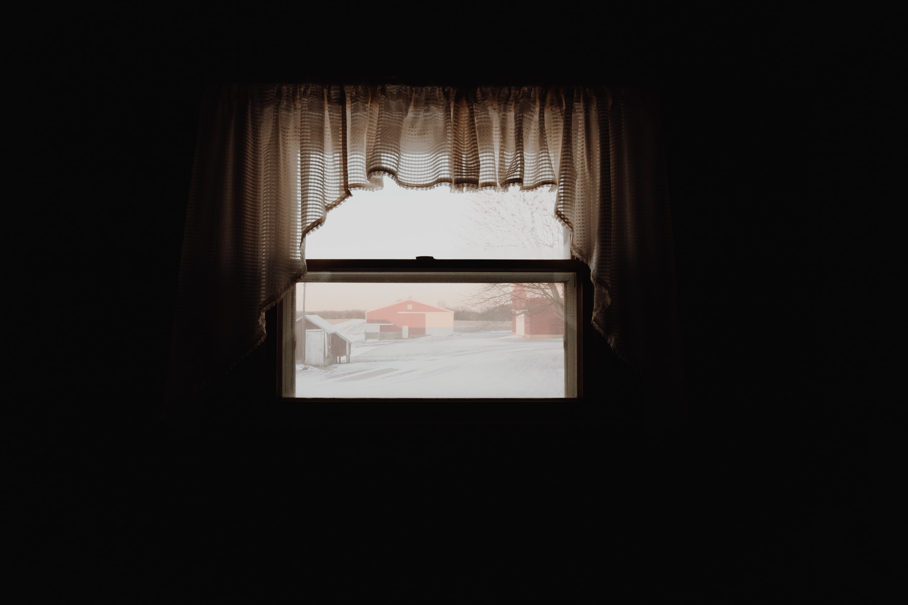 clear glass window with white curtain