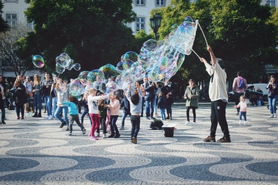 group of people playing bubble at park performance art teams background