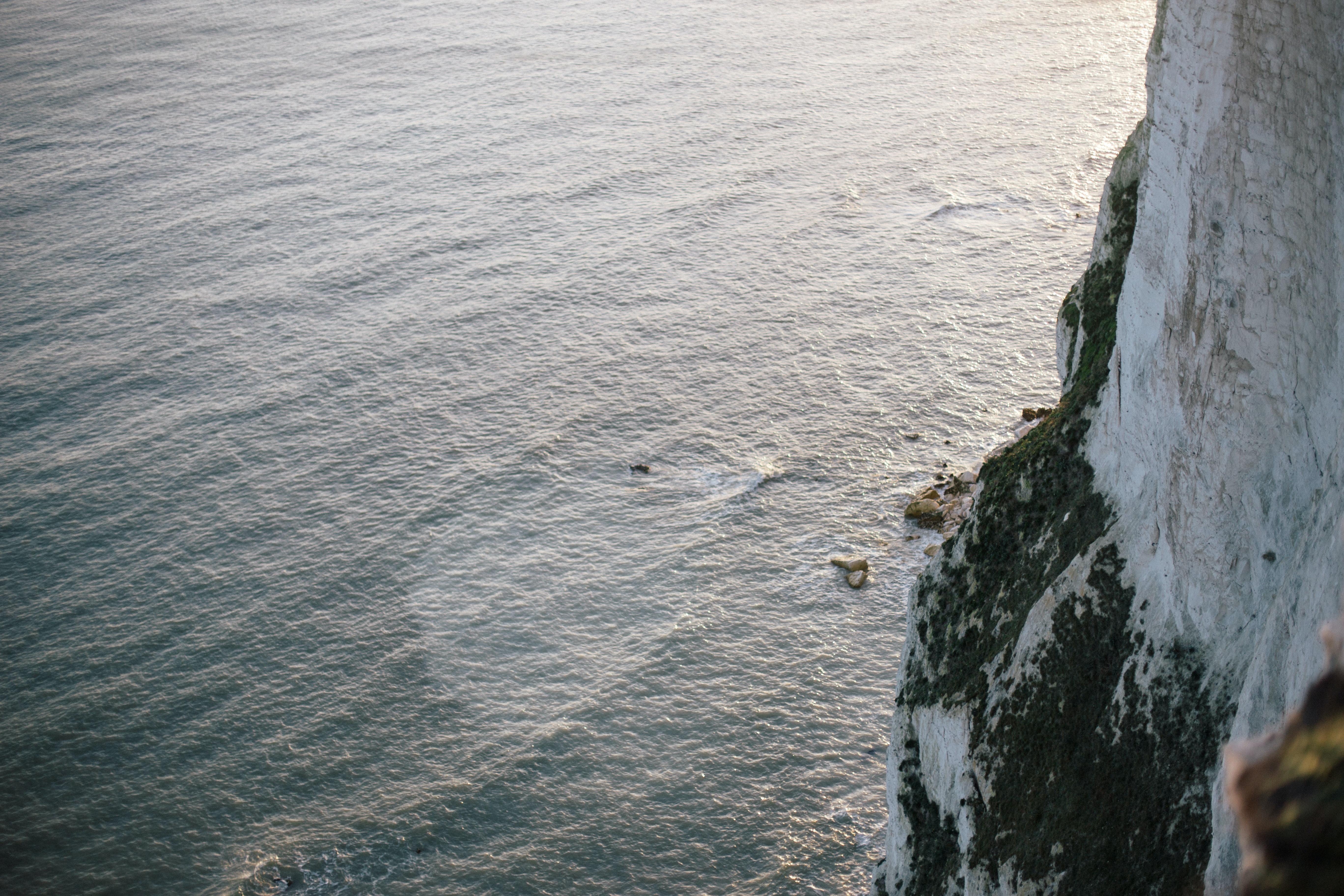 white rocky mountain next to ocean