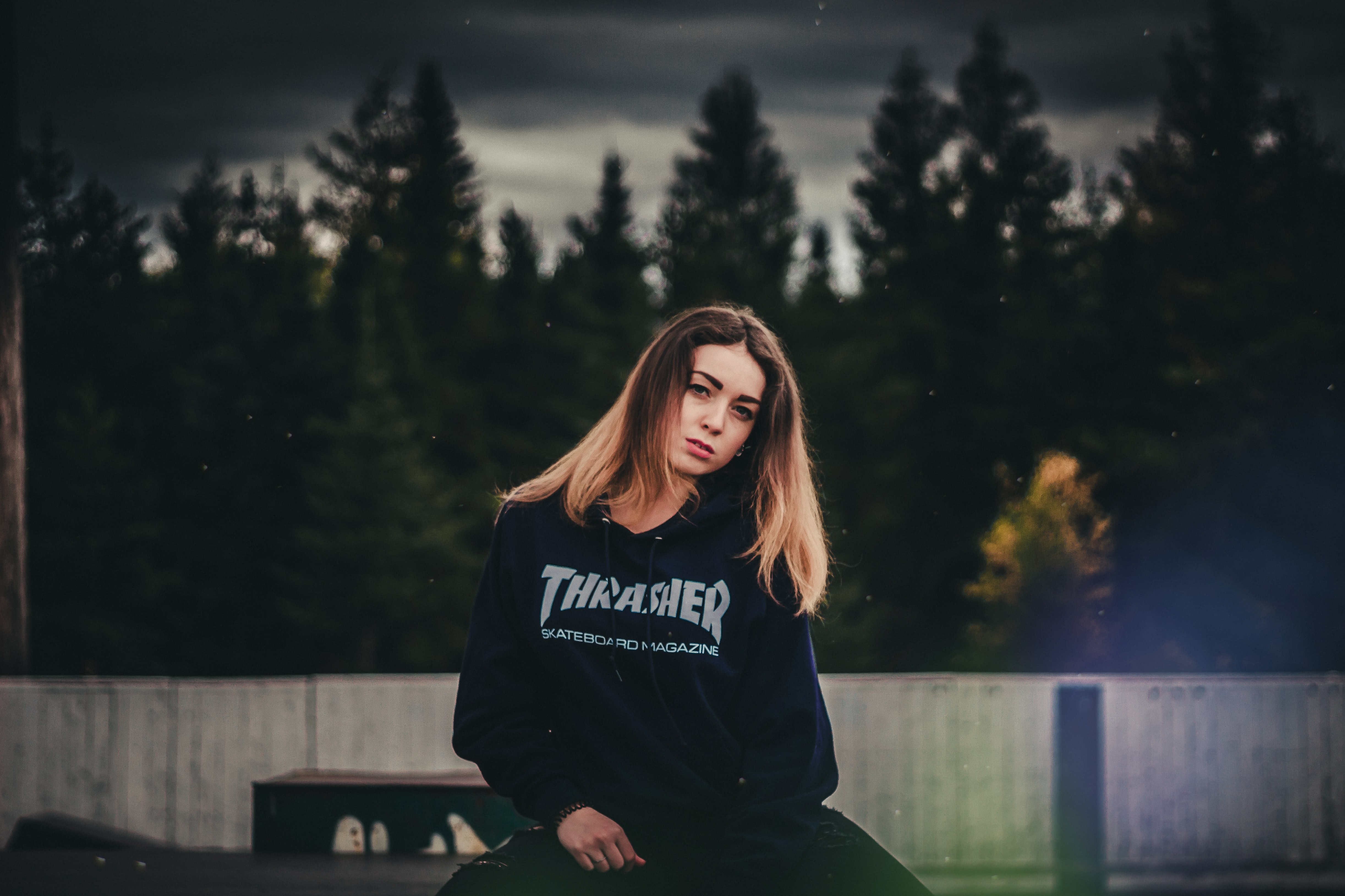 woman wearing Trasher pullover hoodie standing in front of concrete fence and trees