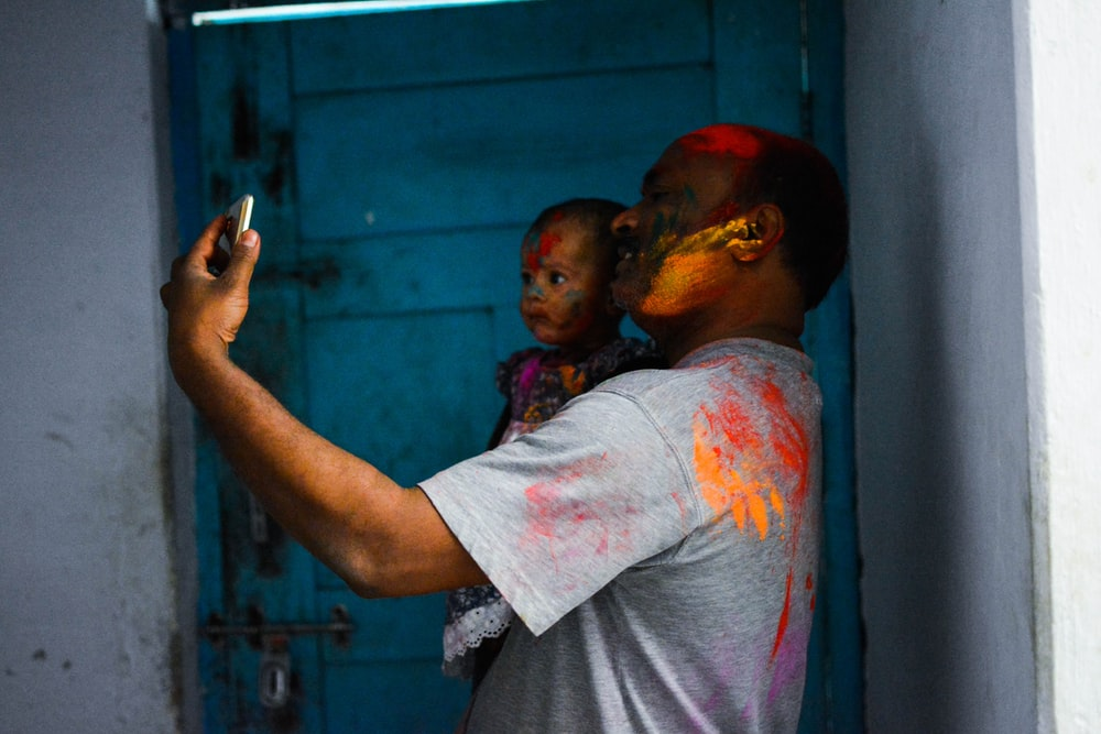 man carrying child while taking selfie