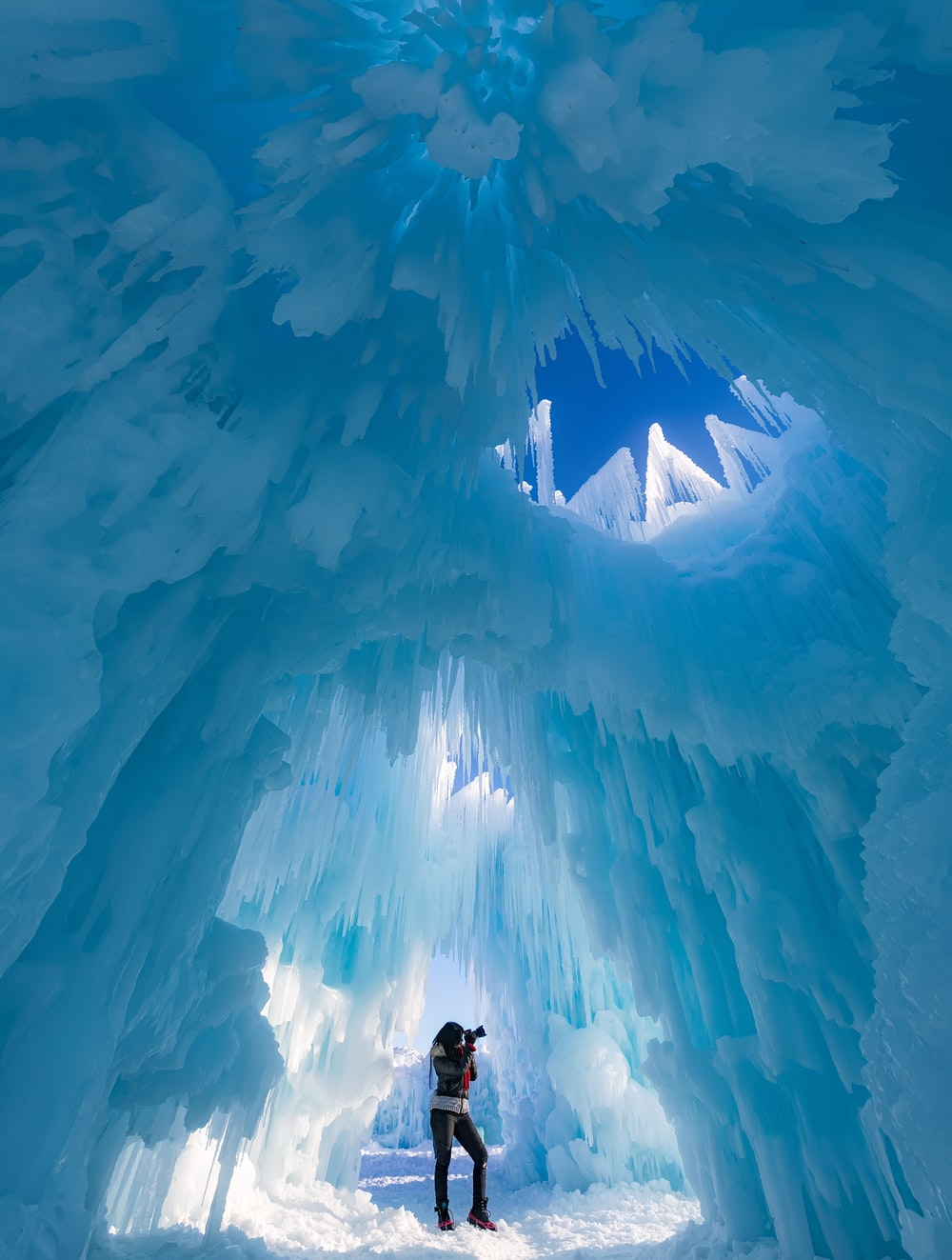 woman taking photograph in ice cave