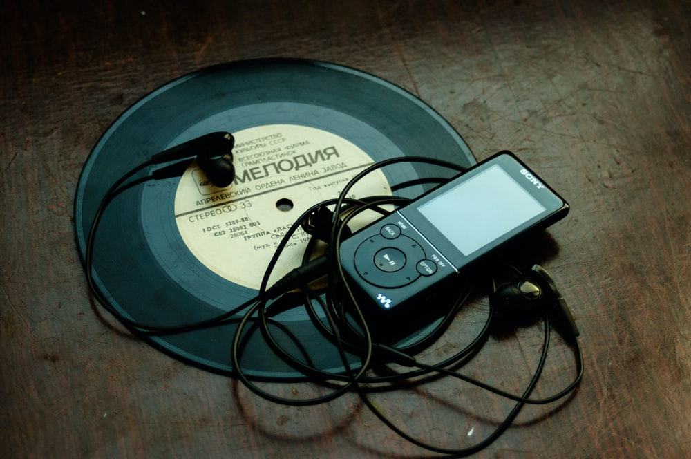 in-ear headphones plugged in black Sony Walkman on vinyl record