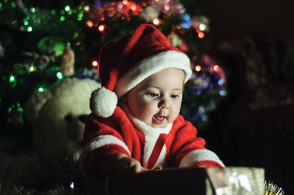 baby wearing Santa Claus outfit near Christmas tree