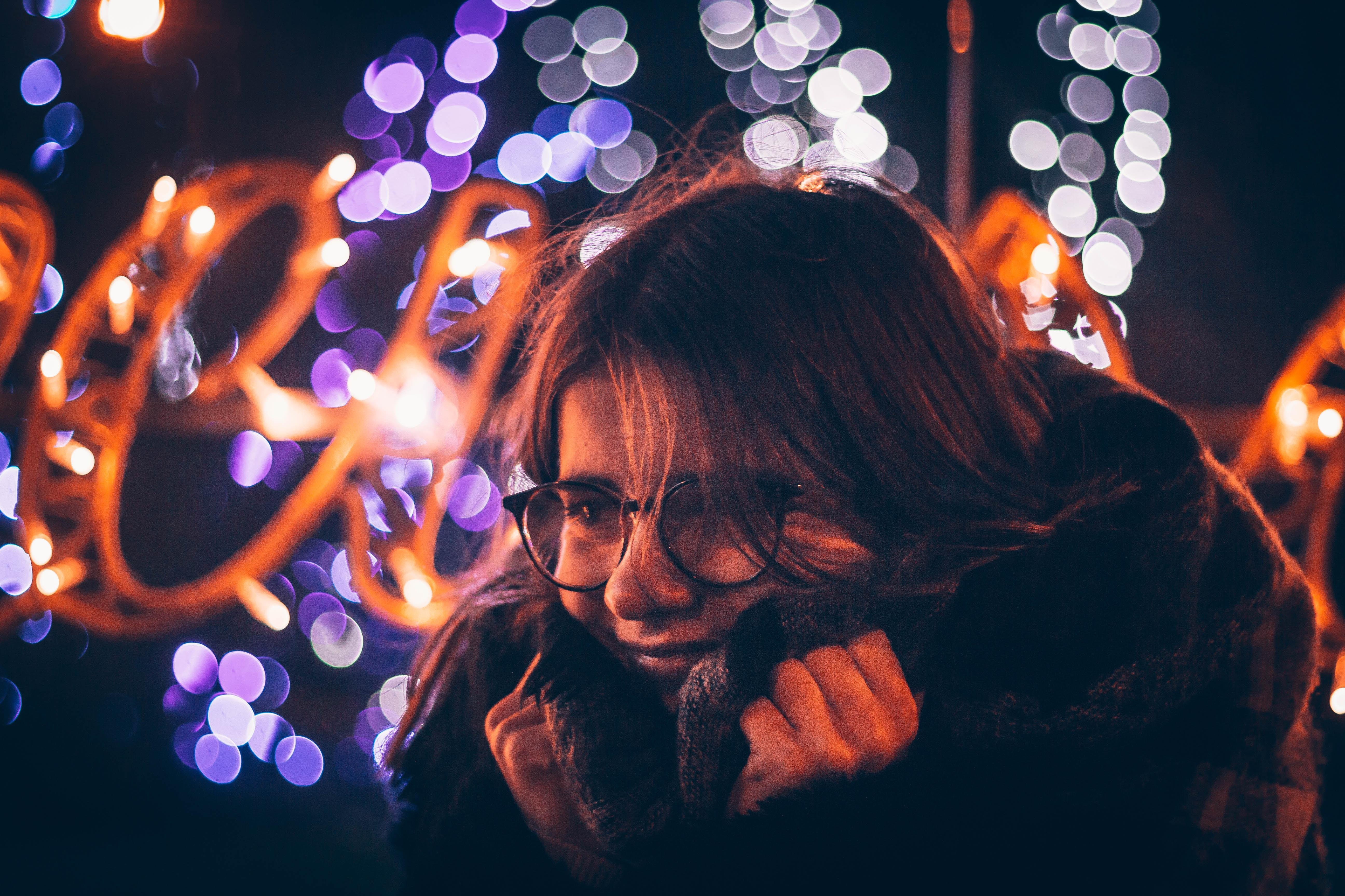 bokeh photography of woman holding coat wearing eyeglasses