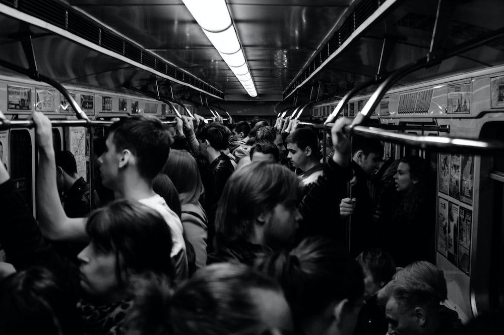 grayscale photography of people riding train