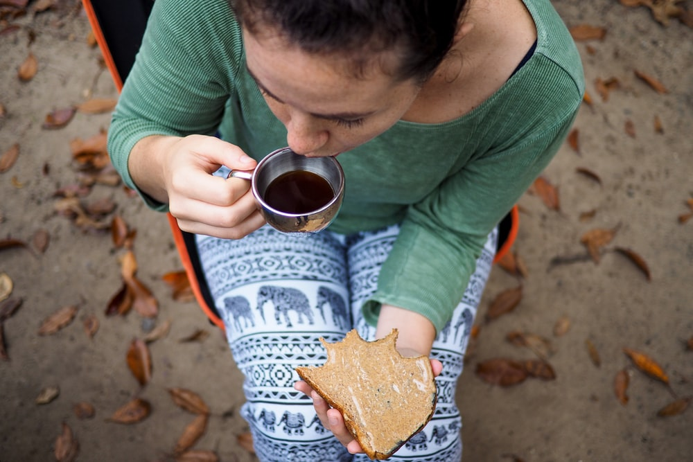 woman holding gray steel cup and toast outdoor during daytime