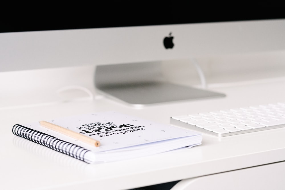 white book beside iMac and keyboard on table