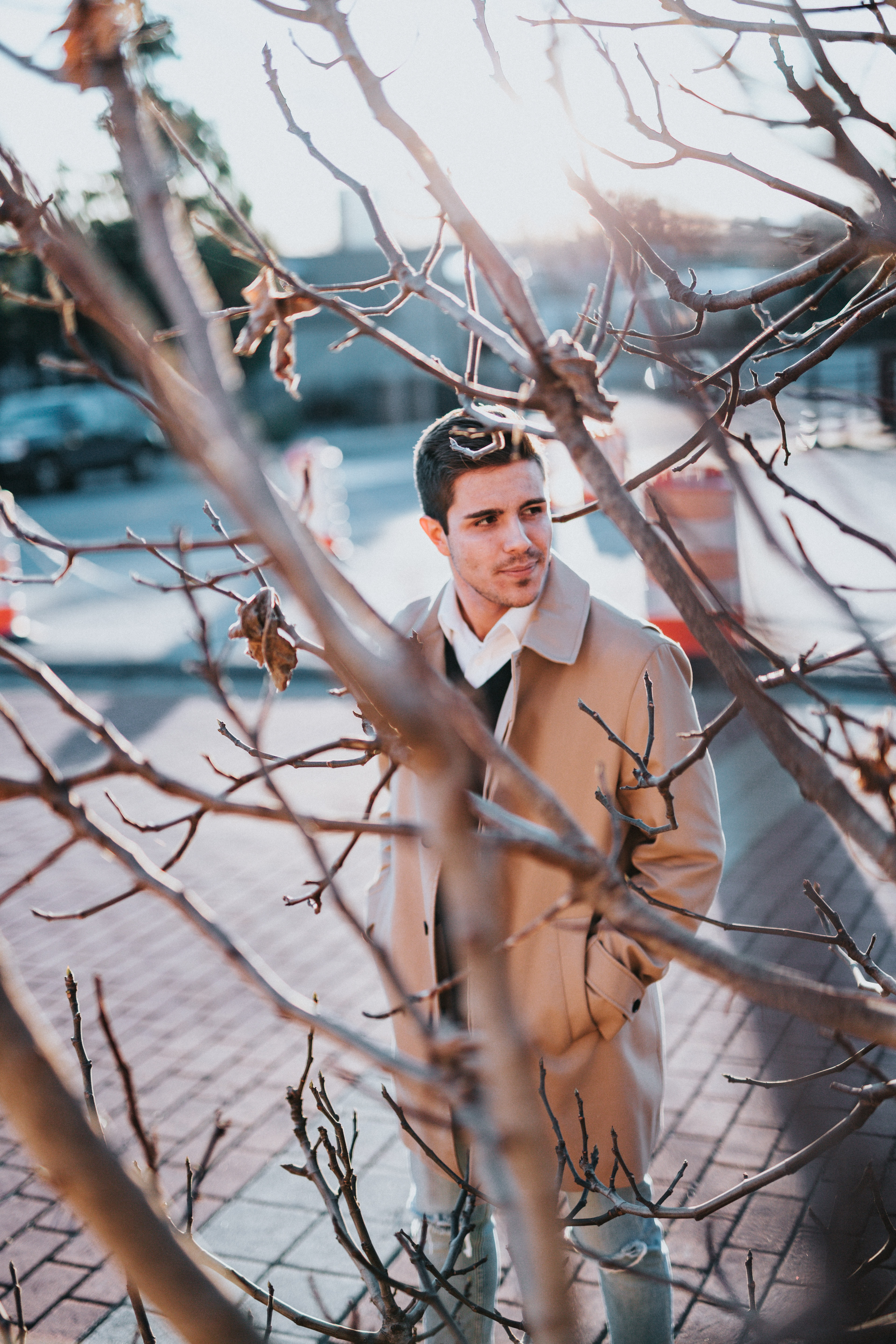 man wearing brown coat standing near tree