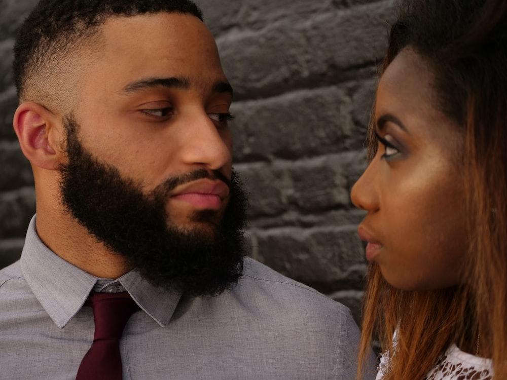 man staring at woman near gray concrete wall