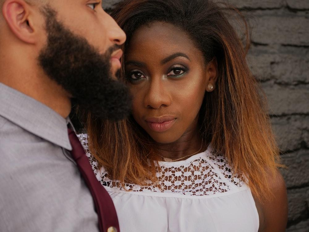 woman wearing white shirt beside man wearing grey shirt and necktie