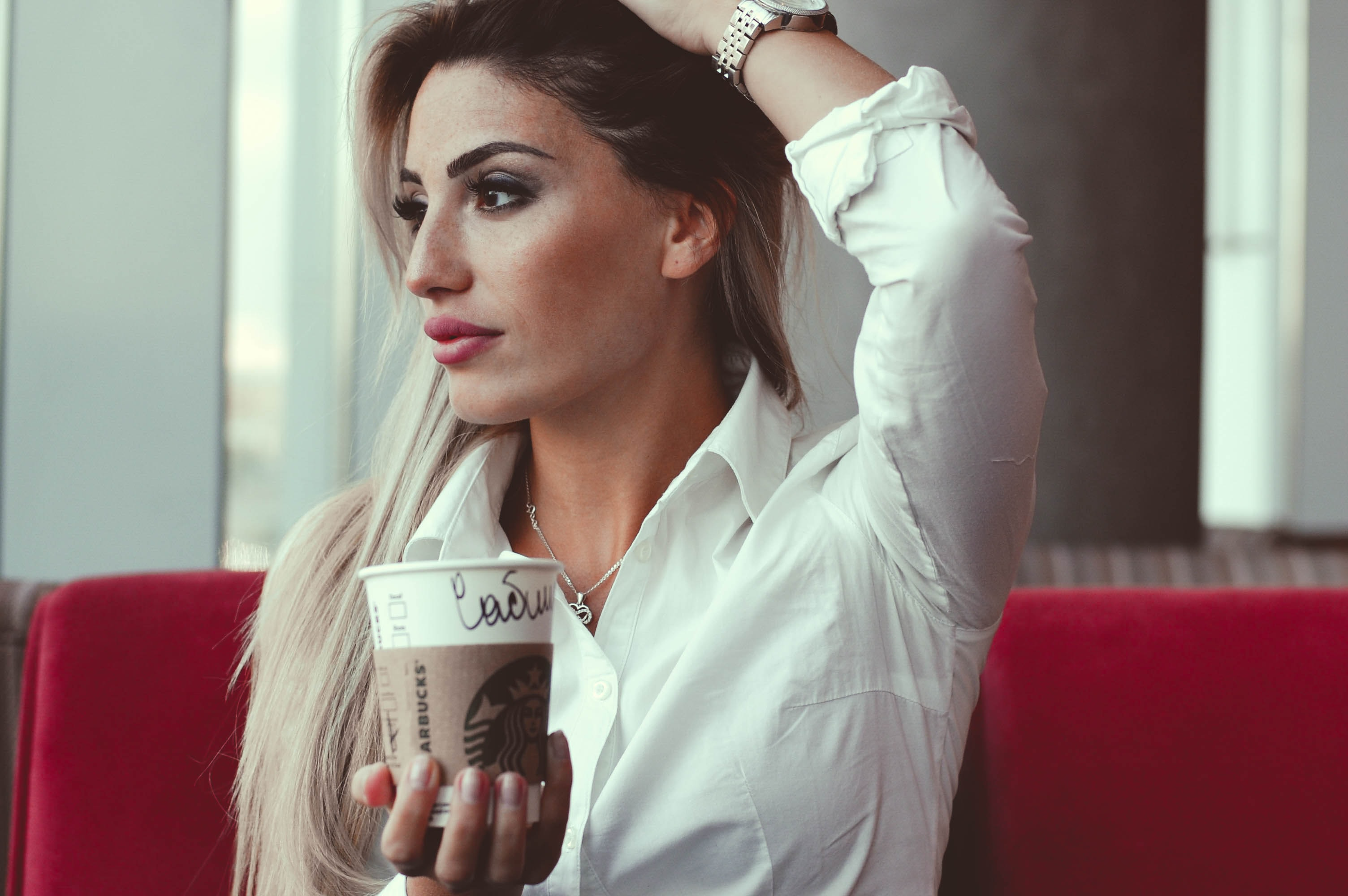 selective focus photo of woman taking post while holding white disposable cup