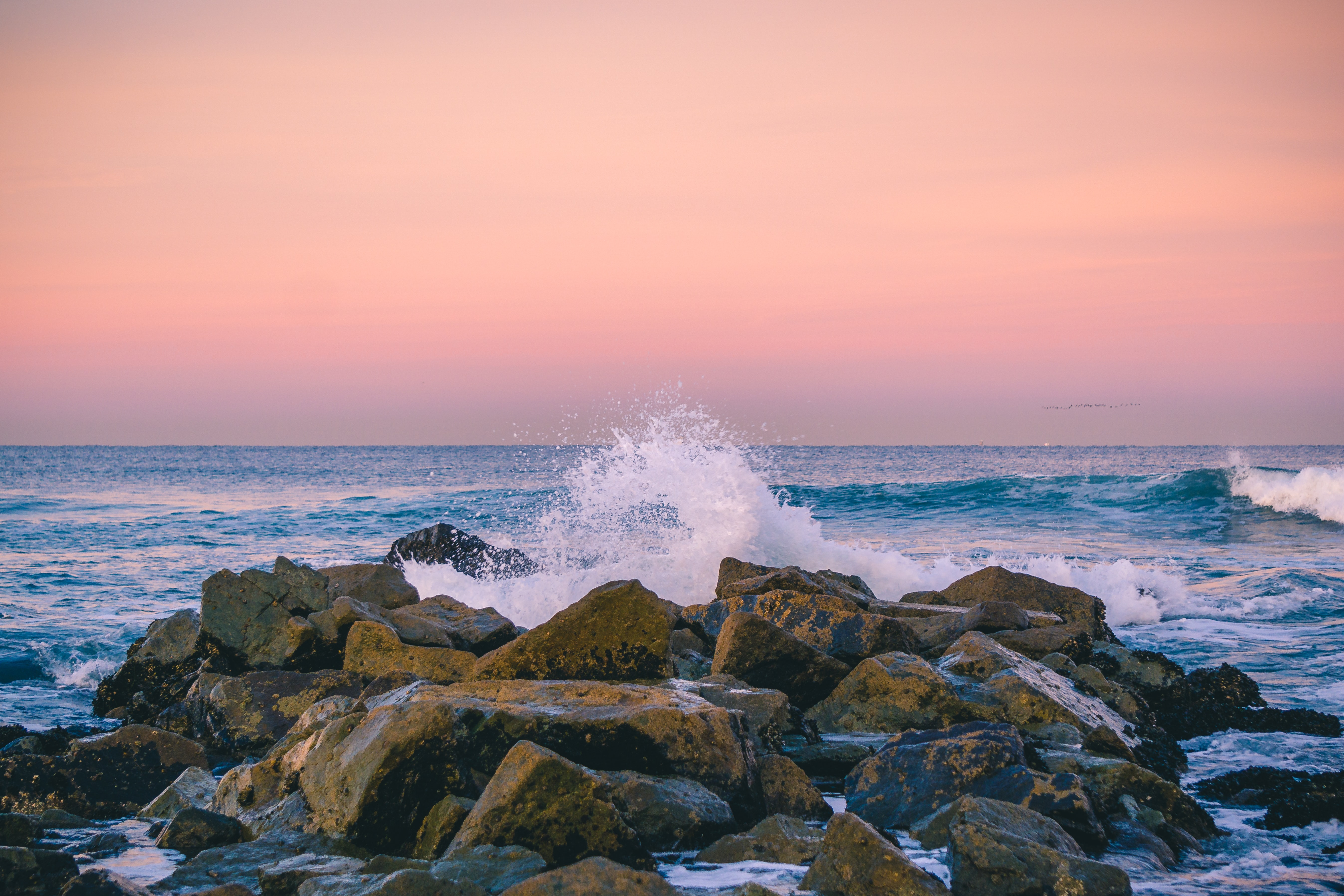 rocks surrounded by ocean during sunset