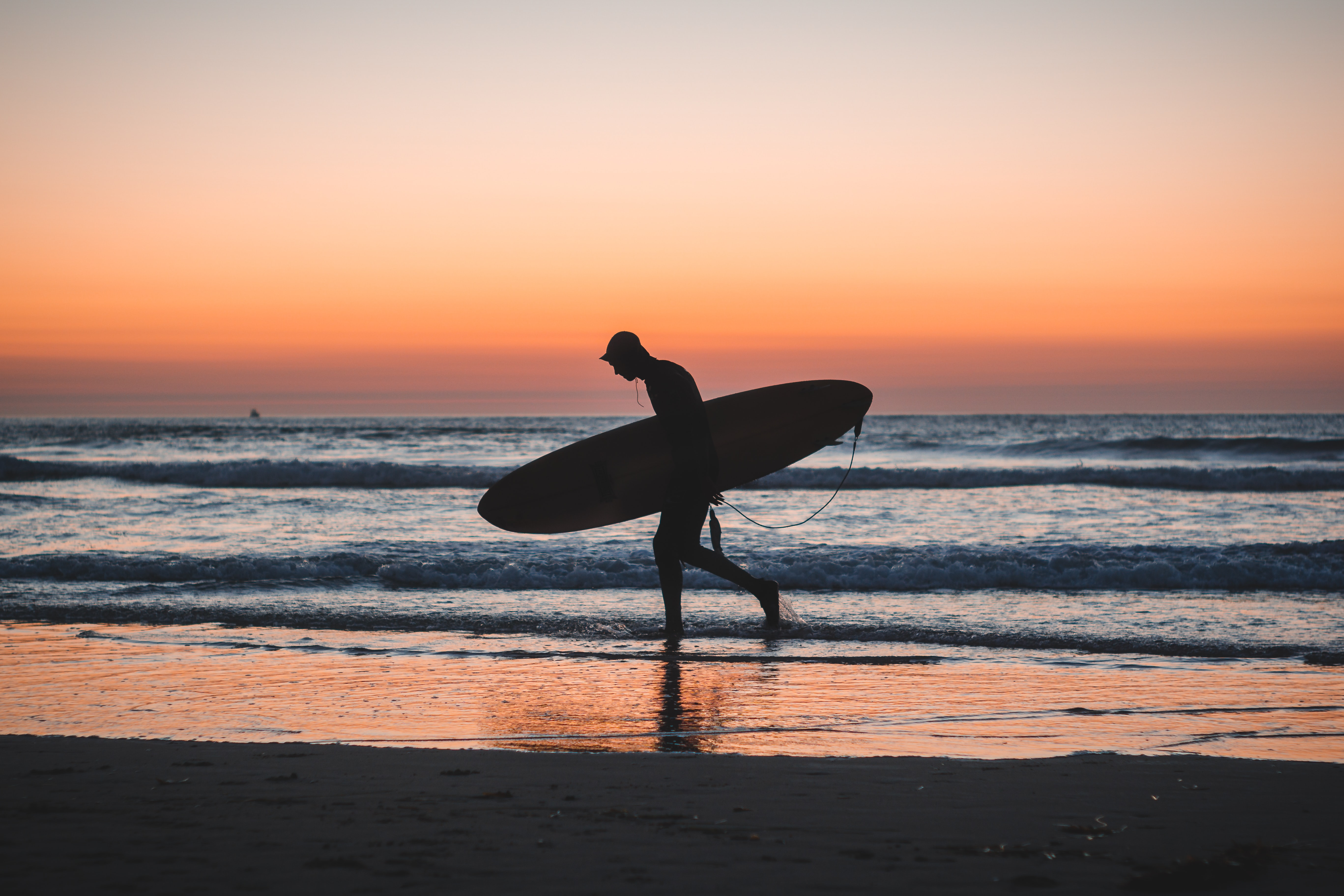 silhouette photo of person holding surfboard near shore