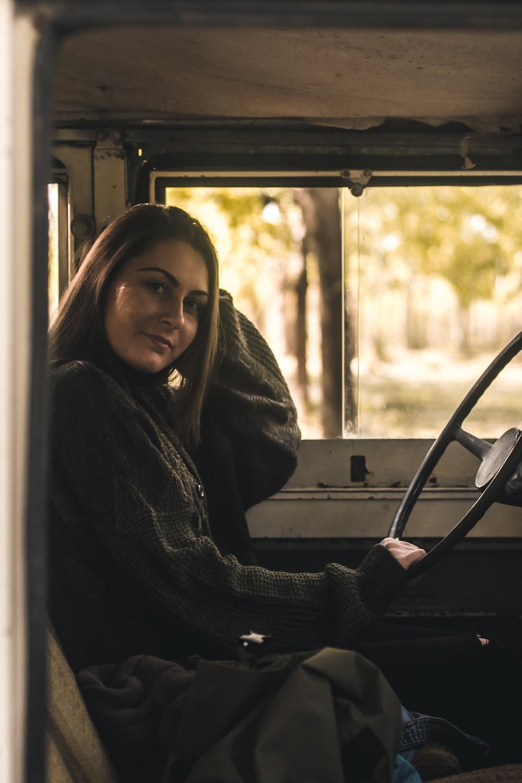 woman sitting inside vehicle holding steering wheel during daytime