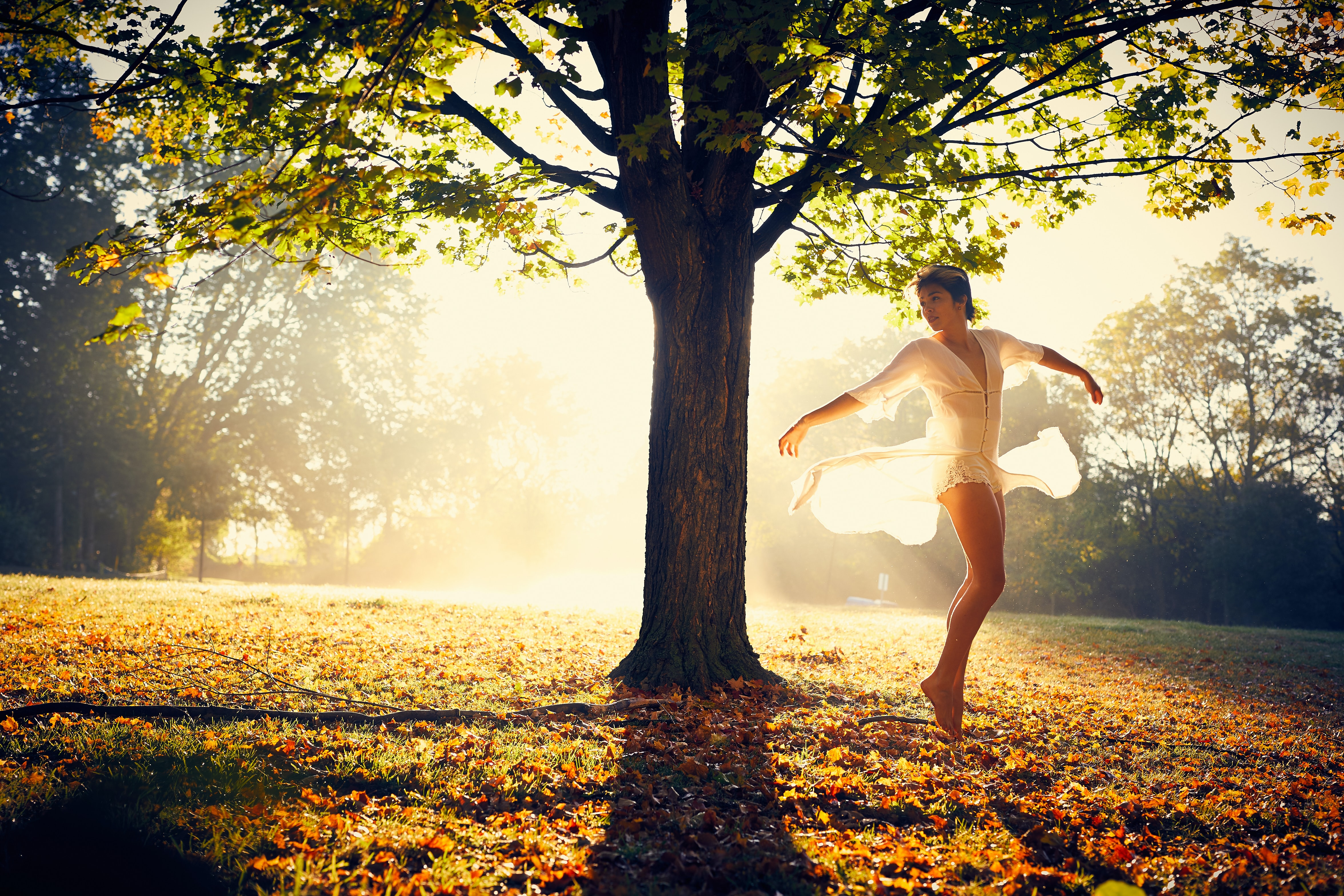 woman spreading arms beside tree during daytime
