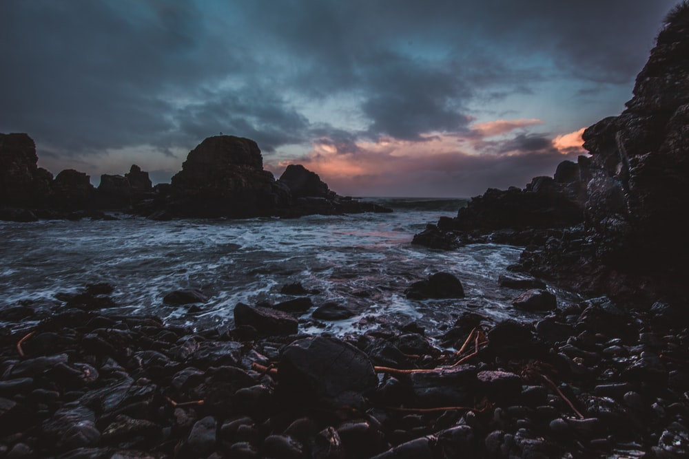 rocky body of water under gray sky