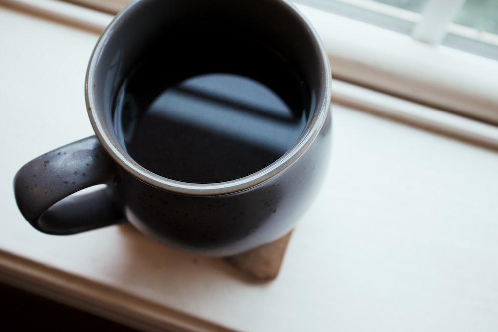 black ceramic mug on white panel