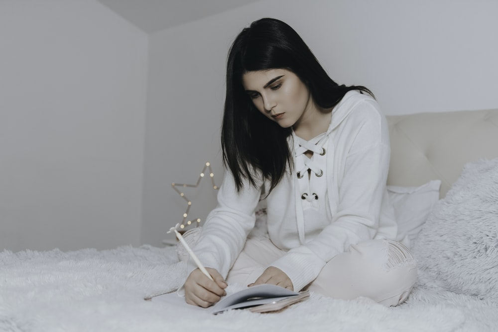 woman sitting on bed while writing on notebook