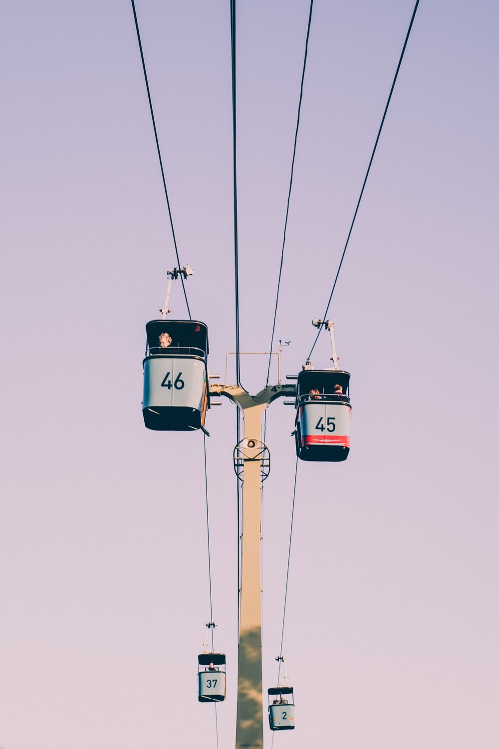 four black-and-gray cable cars crossing