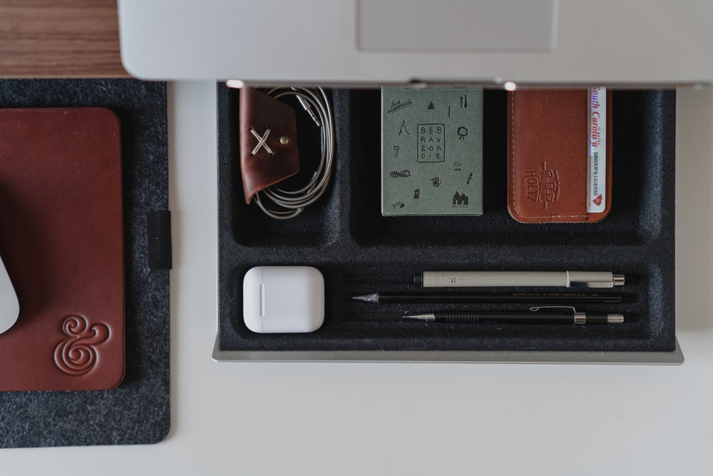 opened drawer with pens and purse in iot