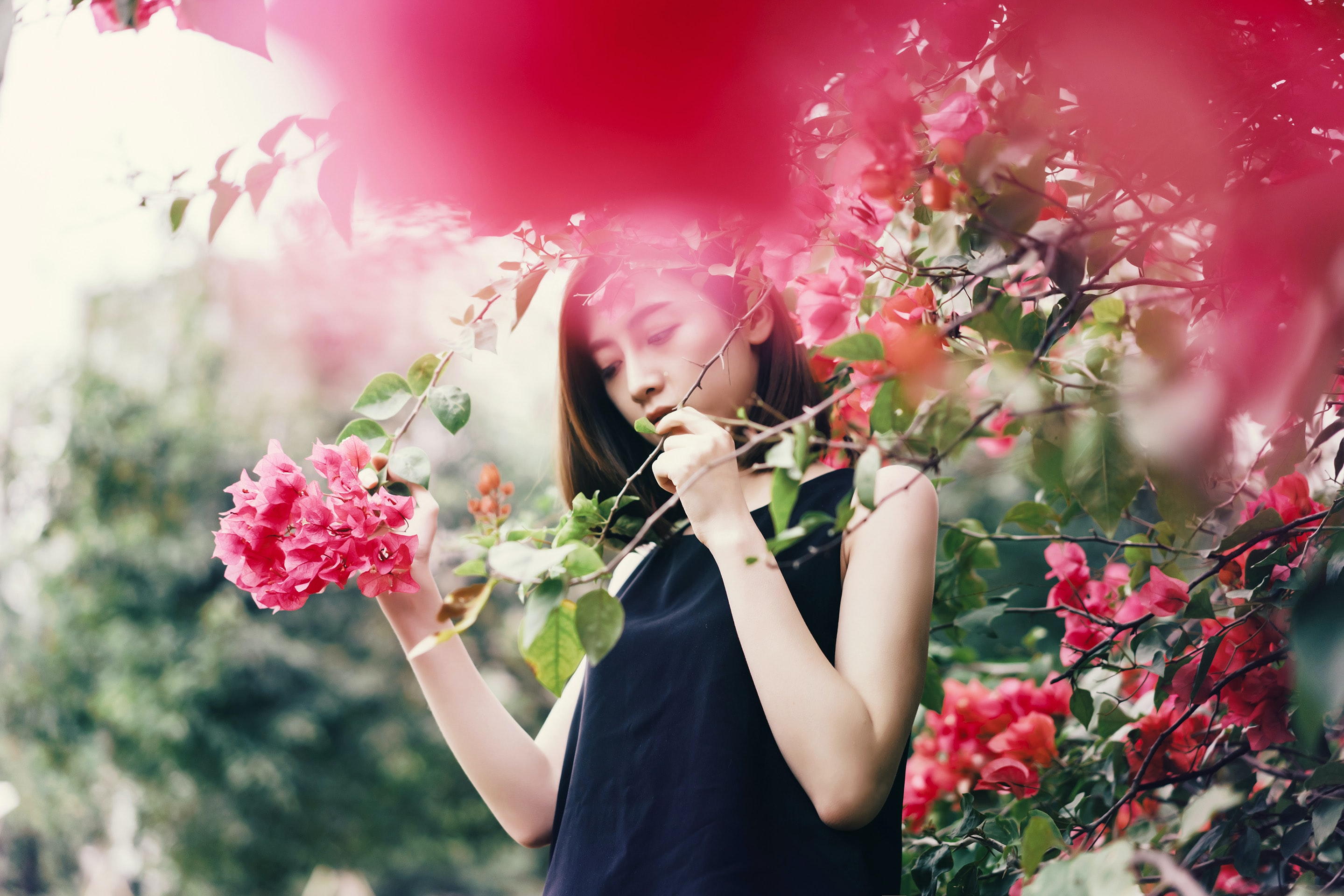 woman in black sleeveless top holding branch of plants with red flowers