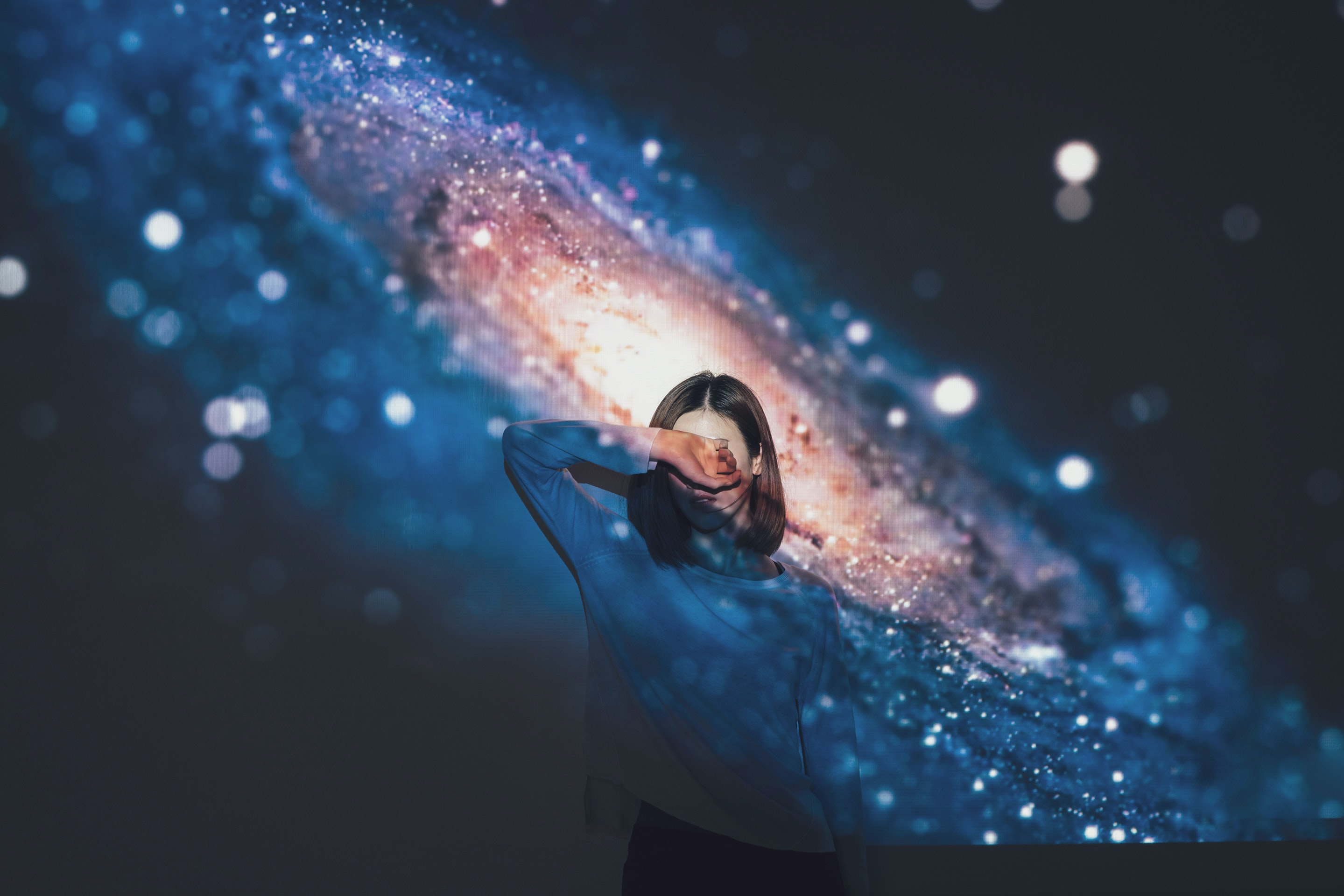 woman covering her face using right hand with galaxy background