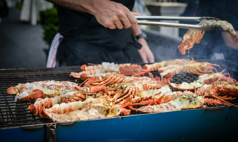 man grilling crabs during daytime