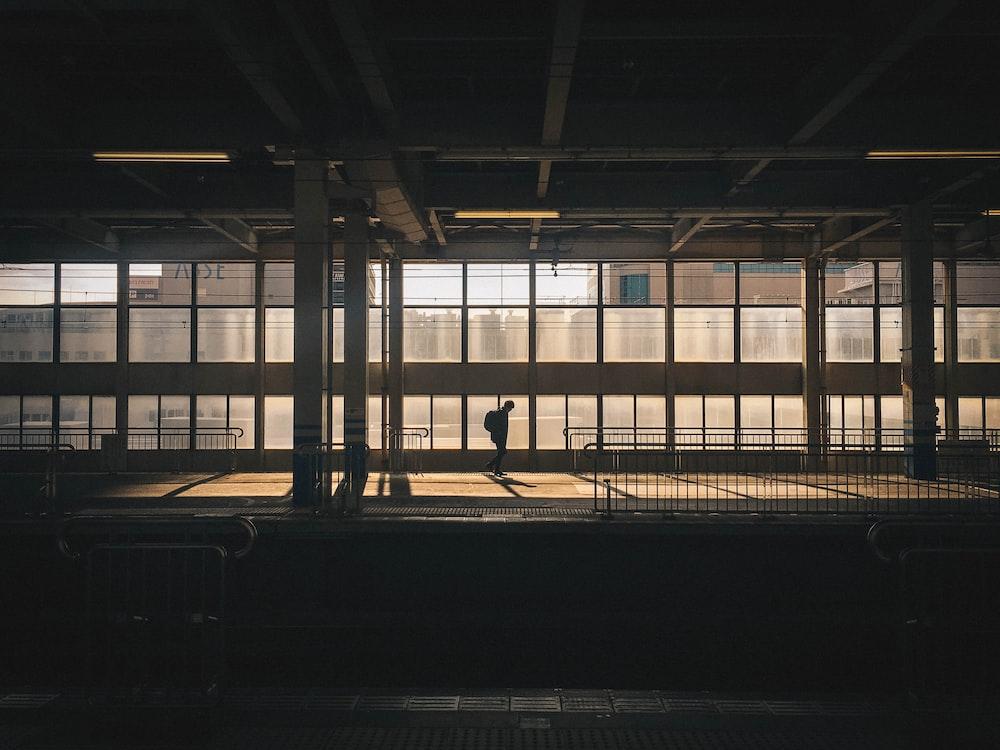 man standing inside building near window