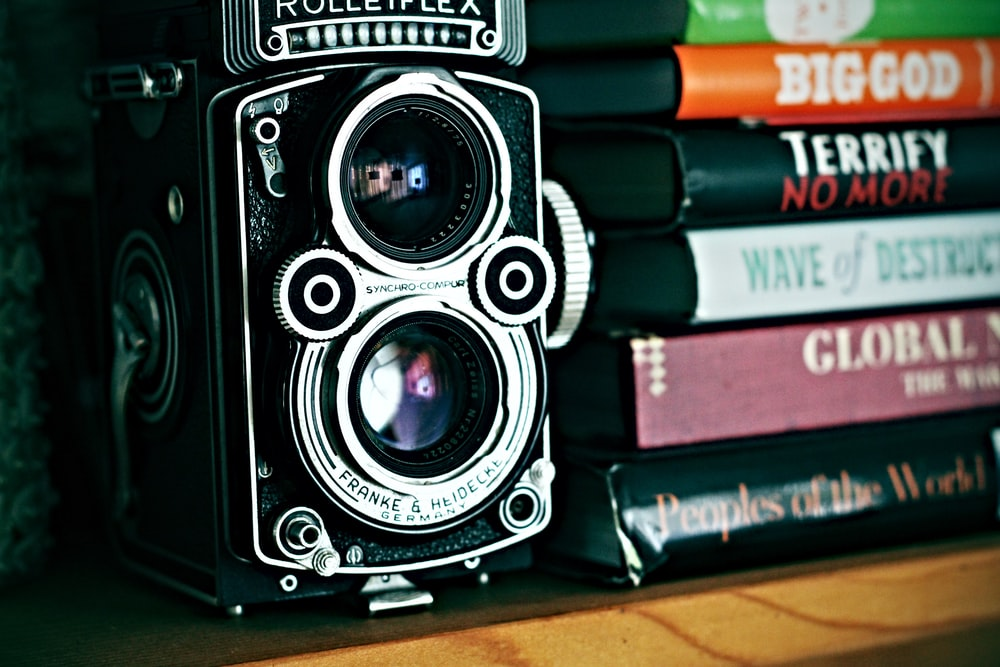vintage camera beside stack of books