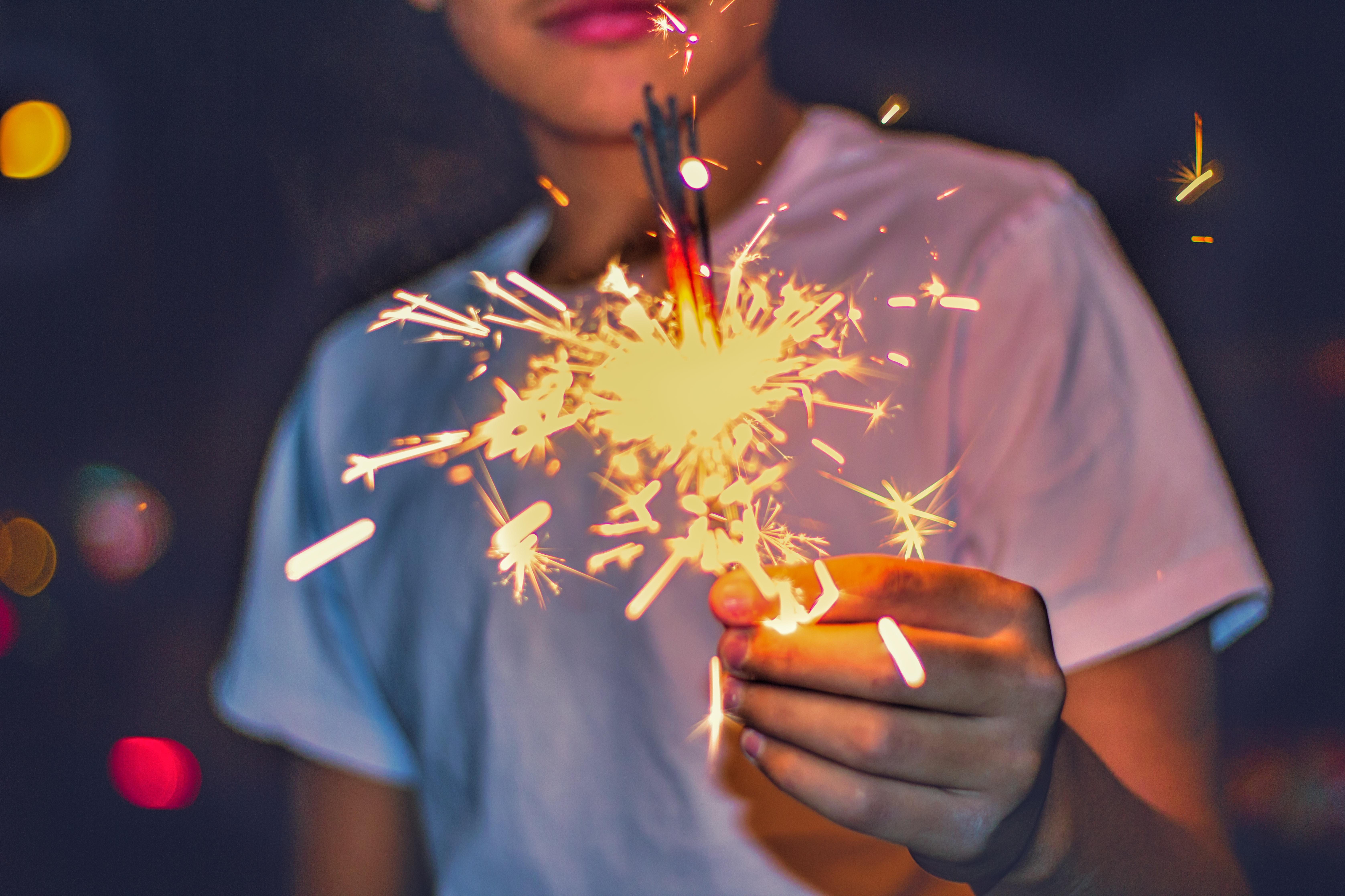 boy holding sparkler bokeh photo