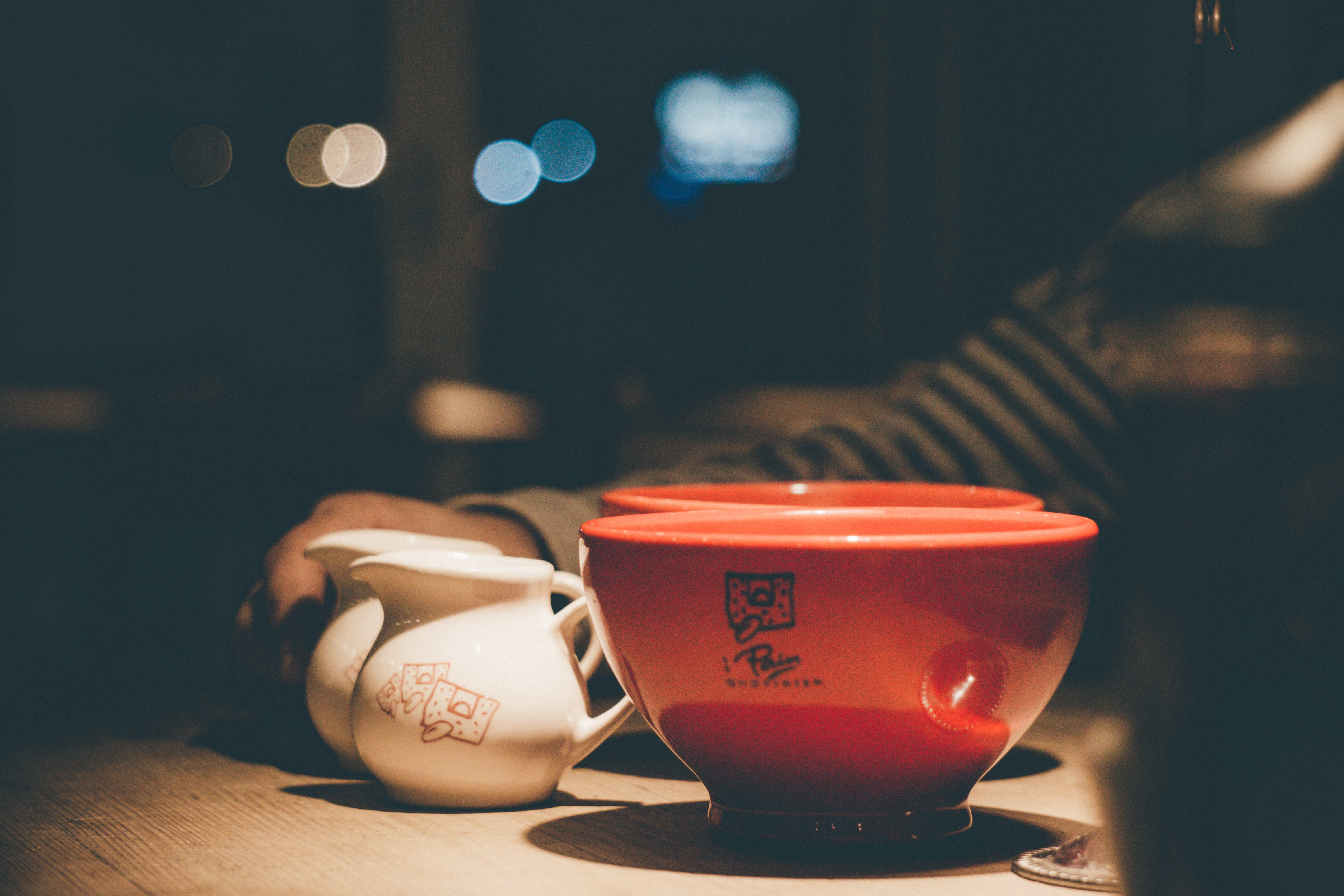 selective focus photography of two red ceramic bowls near two white ceramic pitchers
