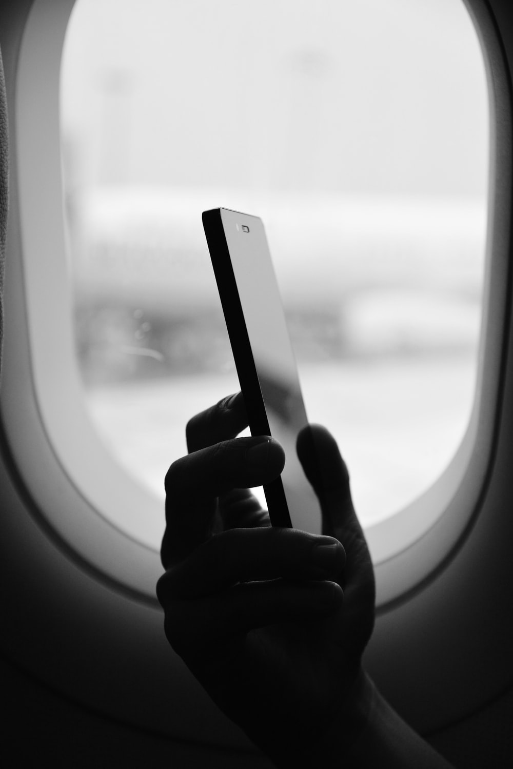 grayscale photography of person holding smartphone beside window
