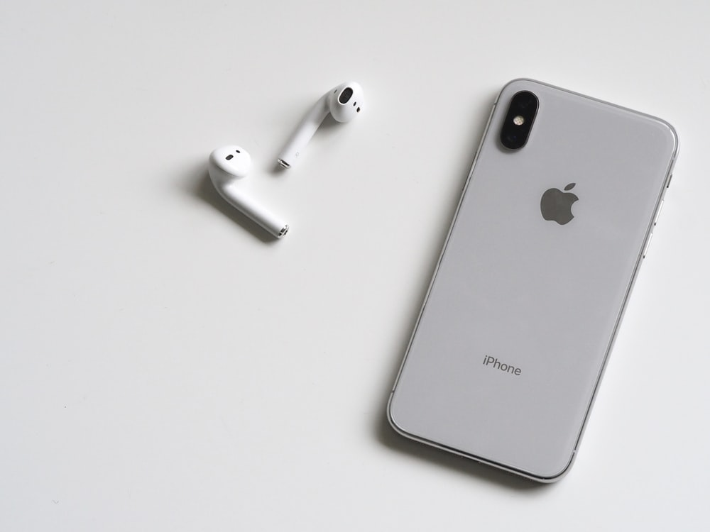 silver iPhone X and Apple EarPods