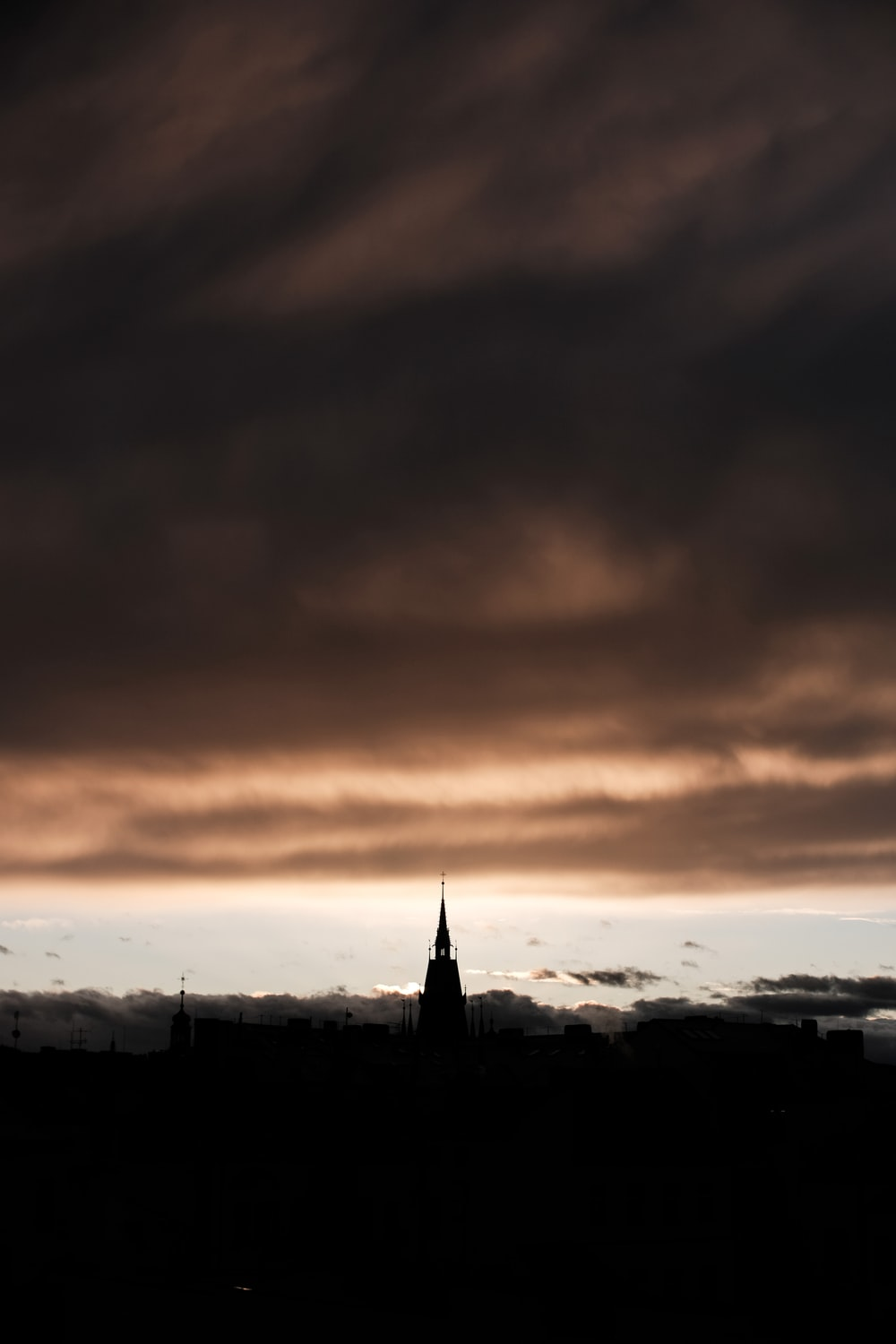 silhouette of tower under gray clouds during daytime