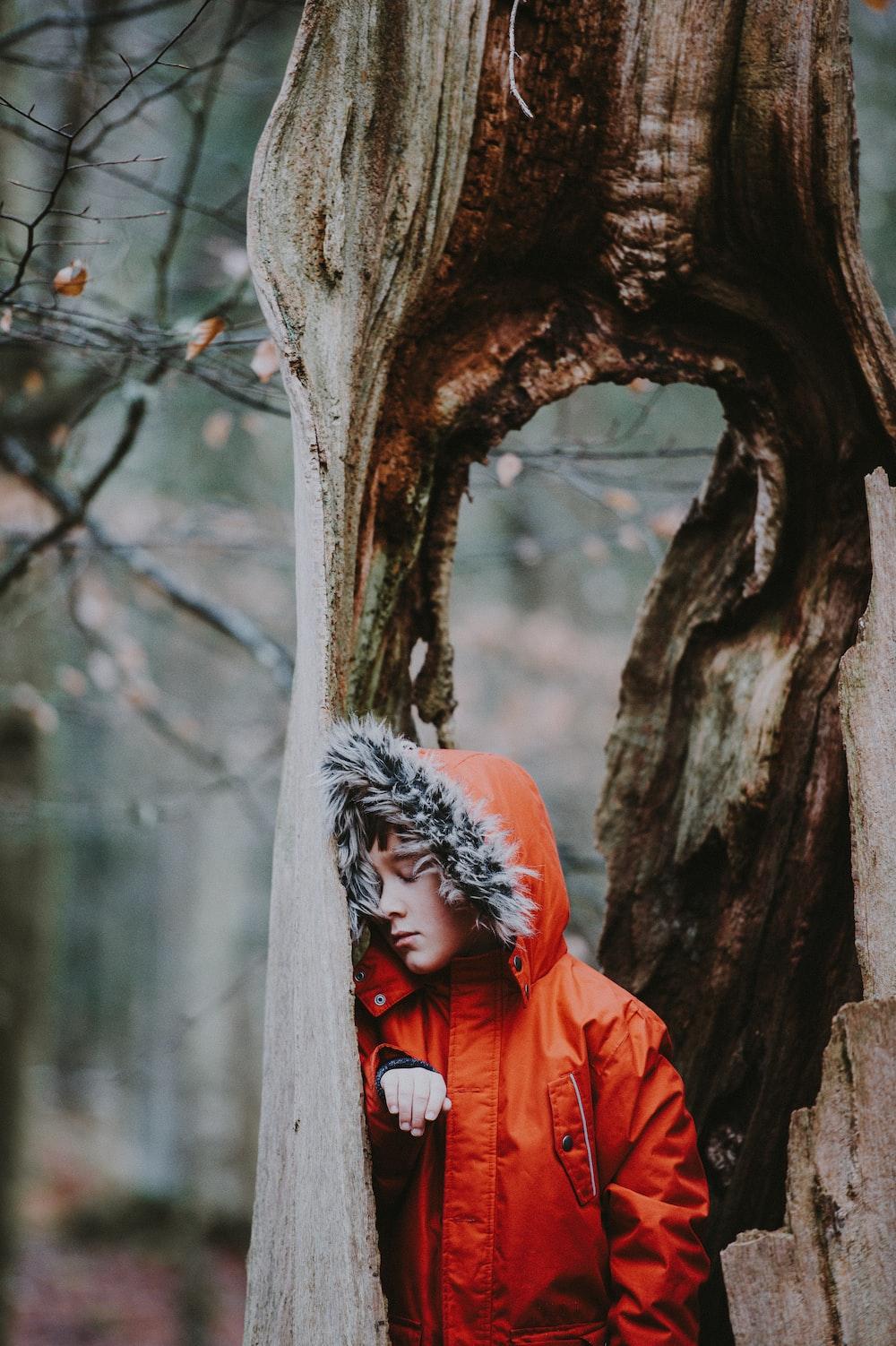 boy leaning on tree trunk