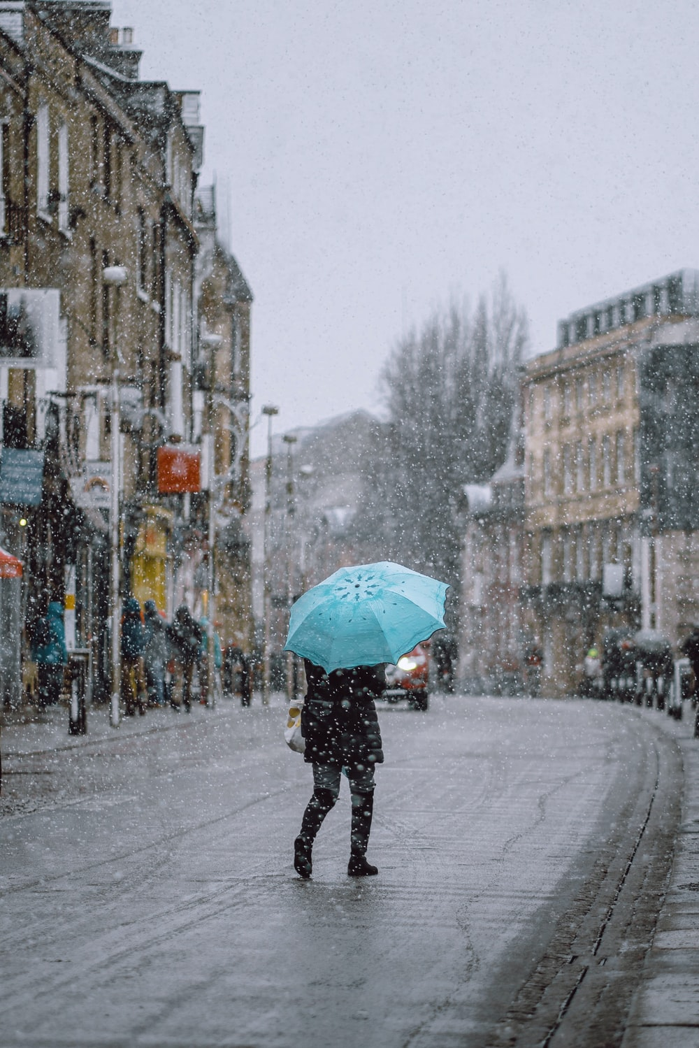 person using blue umbrella walking on street with falling snow