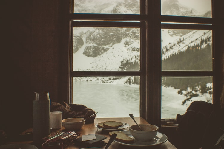 A photo of a breakfast table covered in dishes, in front of a window looking out on a snowy landscape. The colours are all muted.