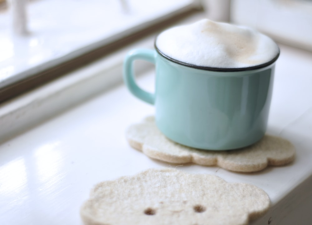 teal ceramic mug with creams near window